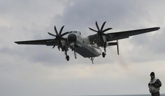 In this March 14, 2017, file photo, a U.S. Navy C-2 Greyhound approaches the deck of the Nimitz-class aircraft carrier USS Carl Vinson during the annual joint military exercise called Foal Eagle between South Korea and the United States at an unidentified location in the international waters, east of the Korean Peninsula. A similar type of the U.S. Navy plane carrying 11 crew and passengers crashed into the Pacific Ocean on Wednesday, Nov. 22, 2017, while on the way to the USS Ronald Reagan aircraft carrier, the Navy said. (AP Photo/Lee Jin-man, File)