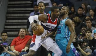 Washington Wizards guard John Wall, left, drives into Charlotte Hornets guard Kemba Walker in the first half of an NBA basketball game in Charlotte, N.C., Wednesday, Nov. 22, 2017. (AP Photo/Nell Redmond)