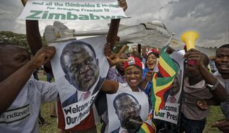 Supporters of Emmerson Mnangagwa, the man expected to become Zimbabwe's new president, hold a photograph of him and cheer as they arrive to show their support at Manyame Air Force base where Mnangagwa is expected to arrive later in the day in Harare, Zimbabwe Wednesday, Nov. 22, 2017. Mugabe resigned as president with immediate effect Tuesday after 37 years in power, shortly after parliament began impeachment proceedings against him. (AP Photo/Ben Curtis)