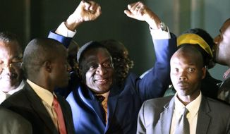 Zimbabwe's incoming leader Emmerson Mnangagwa, centre, gestures as he greets the crowd upon arrival at the Zanu PF  Headquarters in Harare, Wednesday, Nov, 22, 2017.  Mnangagwa has emerged from hiding and returned home ahead of his swearing-in Friday. Crowds have gathered at the ruling party's headquarters for his first public remarks. Mnangagwa will replace Robert Mugabe, who resigned after 37 years in power when the military and ruling party turned on him for firing Mnangagwa and positioning his wife to take power. (AP Photo/Tsvangirayi Mukwazhi)
