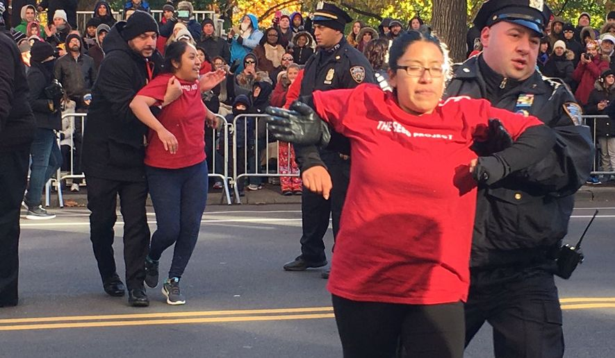 "Several protesters tried to stage a demonstration by rushing out into the street and sitting down in the middle of the parade route as a band marched by. The protesters wore red T-shirts and chanted ""Undocumented, unafraid,"" which has become a motto of the illegal immigrant community demanding an amnesty. (photograph via https://twitter.com/ajplus)"