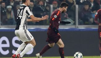 Barcelona's Lionel Messi is challenged by Juventus' Daniele Rugani, left, during the Champions League group D soccer match between Juventus and Barcelona, at the Allianz Stadium in Turin, Italy, Wednesday, Nov. 22, 2017. (AP Photo/Antonio Calanni)