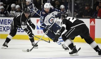 Winnipeg Jets right wing Blake Wheeler, center, moves the puck between Los Angeles Kings center Anze Kopitar, left, of Slovenia, and defenseman Derek Forbort during the first period of an NHL hockey game, Wednesday, Nov. 22, 2017, in Los Angeles. (AP Photo/Mark J. Terrill)