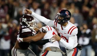 Mississippi quarterback Jordan Ta'amu, right, passes as a Mississippi State defender rushes him during the first half of an NCAA college football game in Starkville, Miss., Thursday, Nov. 23, 2017. (AP Photo/Rogelio V. Solis)
