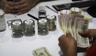 In this July 1, 2017 file photo, a person buys marijuana at the Essence cannabis dispensary in Las Vegas. (AP Photo/John Locher, File)