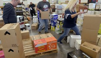 Employees at the Cottonwood Heights, Utah, state liquor store sort through a shipment of spirits on Wednesday, Nov. 22, 2017. (Al Hartmann/The Salt Lake Tribune via AP)