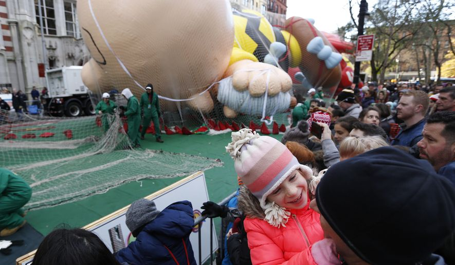Emily Newman, 7, plays with her father as they watch the balloons being inflated for the Thanksgiving Day parade in New York, Wednesday, Nov. 22, 2017. (AP Photo/Seth Wenig)