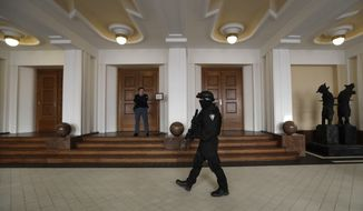 A prison guard walks outside a courtroom during an appeal by Yevgeniy Nikulin from Russia who faces charges of hacking computers of American companies, Friday, Nov. 24, 2017, in Prague, Czech Republic. Czech authorities arrested Nikulin in Prague in cooperation with the FBI in October last year. He is accused by U.S. prosecutors of penetrating computers at Silicon Valley firms including LinkedIn and Dropbox in 2012. (AP Photo/Petr David Josek)