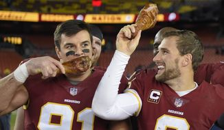 Washington Redskins quarterback Kirk Cousins (8) holds up a turkey leg as outside linebacker Ryan Kerrigan (91) eats his after an NFL football game against the New York Giants in Landover, Md., Friday, Nov. 24, 2017. The Redskins defeated the Giants 20-10. (AP Photo/Nick Wass)