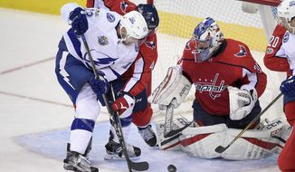 Tampa Bay Lightning center Cedric Paquette (13) fights for the puck against Washington Capitals defenseman Taylor Chorney (4) and goalie Philipp Grubauer (31), of Germany, during the third period of an NHL hockey game, Friday, Nov. 24, 2017, in Washington. The Capitals won 3-1. (AP Photo/Nick Wass)