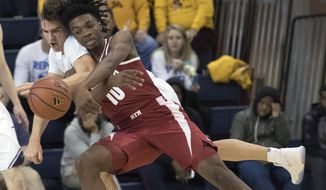 Alabama guard Herb Jones (10) and BYU guard Zac Seljaas fight for a loose ball during the first half of an NCAA basketball game, Friday, Nov. 24, 2017, in New York. (AP Photo/Mary Altaffer)