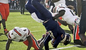 Pittsburgh quarterback Kenny Pickett (8) flips over Miami defensive back Jaquan Johnson (4) as he goes in for a touchdown in the first half of an NCAA college football game, Friday, Nov. 24, 2017, in Pittsburgh. (AP Photo/Keith Srakocic)