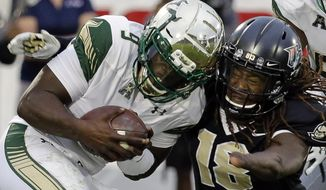 South Florida quarterback Quinton Flowers (9) escapes a tackle by Central Florida linebacker Shaquem Griffin during the first half of an NCAA college football game, Friday, Nov. 24, 2017, in Orlando, Fla. (AP Photo/John Raoux)