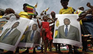 A young girl marches in position as she mimics the military parade, accompanied by supporters holding posters of President Emmerson Mnangagwa, at his inauguration ceremony in the capital Harare, Zimbabwe Friday, Nov. 24, 2017. Mnangagwa was sworn in as Zimbabwe's president after Robert Mugabe resigned on Tuesday, ending his 37-year rule. (AP Photo/Ben Curtis)
