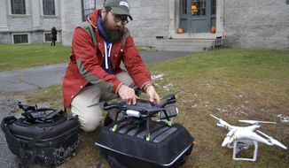 In this Nov. 14, 2017 photo, Dartmouth's Chad Hill readies a drone to be flown over a site of a Shaker Village in Enfield, NH. Hill and his Dartmouth colleague Jesse Casana are using drones equipped with thermal imaging cameras to study a half-dozen archaeological sites around the world. The cameras use heat differences between stone and the soil surrounding it to identify structures below the surface like foundations of buildings, which then can be further explored. (AP Photo/Michael Casey)