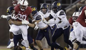 Stanford running back Bryce Love (20) is tackled by a group of California defenders during the first half of an NCAA college football game Saturday, Nov. 18, 2017, in Stanford, Calif. (AP Photo/Marcio Jose Sanchez)