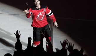 New Jersey Devils center Brian Boyle throws a puck toward fans after he helped the Devils defeat the Vancouver Canucks 3-2 during an NHL hockey game, Friday, Nov. 24, 2017, in Newark, N.J. (AP Photo/Julio Cortez)