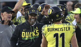 FILE - In this Oct. 28, 2017, file photo, Oregon head coach Willie Taggart congratulates Oregon quarterback Braxton Burmeister after an Oregon score against Utah in the fourth quarter of an NCAA college football game in Eugene, Ore. Oregon and Oregon State head into the 121st Civil War game in Eugene, on Saturday, Nov. 25, 2017, looking very different than last season. (AP Photo/Chris Pietsch, file) **FILE**