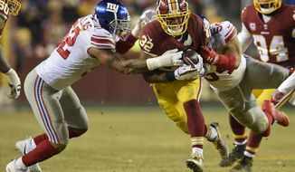 Washington Redskins running back Samaje Perine (32) carries the ball between New York Giants outside linebacker Jonathan Casillas (52) and defensive end Olivier Vernon (54) during the second half of an NFL football game in Landover, Md., Thursday, Nov. 23, 2017. (AP Photo/Nick Wass)