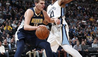 Denver Nuggets center Nikola Jokic, left, of Serbia, drives to the net as Memphis Grizzlies center Deyonta Davis defends in the second half of an NBA basketball game Friday, Nov. 24, 2017, in Denver. The Nuggets won 104-92. (AP Photo/David Zalubowski)