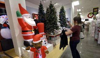 A woman takes photos of artificial Christmas trees while shopping at a J.C. Penney store, Friday, Nov. 24, 2017, in Seattle. (AP Photo/Elaine Thompson) ** FILE **
