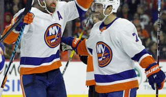 New York Islanders' Andrew Ladd, left, is joined by Jordan Eberle as they celebrate Ladd's game-tying goal during the third period of an NHL hockey game against the Philadelphia Flyers, Nov. 24, 2017, in Philadelphia. The Islanders won 5-4. (AP Photo/Tom Mihalek)