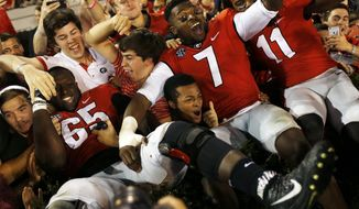 Georgia offensive tackle Kendall Baker (65), outside linebacker Lorenzo Carter (7) and outside linebacker Keyon Brown (11) celebrate with fans after Georgia defeated Kentucky in an NCAA college football game Saturday, Nov. 18, 2017, in Athens, Ga. (Joshua L. Jones/Athens Banner-Herald via AP)