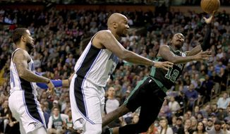 Boston Celtics guard Terry Rozier (12) drives to the basket ahead of Orlando Magic forward Marreese Speights, center, and D.J. Augustin, left, during the first half of an NBA basketball game in Boston, Friday, Nov. 24, 2017. (AP Photo/Mary Schwalm)