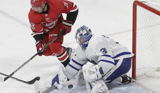 Toronto Maple Leafs goalie Frederik Andersen (31), of Denmark, blocks Carolina Hurricanes' Elias Lindholm (28), of Sweden, during the third period of an NHL hockey game in Raleigh, N.C., Friday, Nov. 24, 2017. (AP Photo/Gerry Broome)
