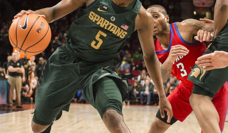 Michigan State guard Cassius Winston, left, dribbles as DePaul's Devin Gage (3) defends during the first half of an NCAA college basketball game at the Phil Knight Invitational tournament in Portland, Ore., Thursday Nov. 23, 2017. (AP Photo/Troy Wayrynen)