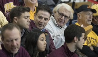 Former Louisville head coach Rick Pitino, third from left, is seen in the stands during the first half of an NCAA college basketball game between Minnesota and UMass, Friday, Nov. 24, 2017, in New York. Minnesota won 69-51. (AP Photo/Mary Altaffer)