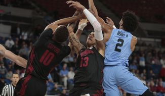 Arkansas' Daniel Gafford, left, and Dustin Thomas, center, fight North Carolina's Joel Berry II, left, for a loose ball in the first half of an NCAA college basketball game during the Phil Knight Invitational tournament in Portland, Ore., Friday, Nov. 24, 2017. (AP Photo/Timothy J. Gonzalez)