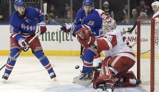 New York Rangers left wing Chris Kreider and center Mika Zibanejad (93) eye the puck as it is deflected by Detroit Red Wings goalie Jimmy Howard (35) during the second period of an NHL hockey game Friday, Nov. 24, 2017, at Madison Square Garden in New York. (AP Photo/Bill Kostroun)