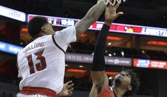 Saint Francis guard Keith Braxton, middle, shoots over Louisville forward Ray Spalding, left, during the first half of an NCAA college basketball game, Friday, Nov. 24, 2017, in Louisville, Ky. (AP Photo/Timothy D. Easley)
