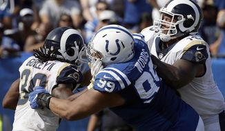 In this Sunday, Sept. 10, 2017 file photo, Indianapolis Colts nose tackle Al Woods (99) stops Los Angeles Rams running back Todd Gurley, left, with offensive guard Rodger Saffold (76) on the block during the second half of an NFL football game in Los Angeles. Defensive tackle Al Woods spent three seasons trying to beat the Indianapolis Colts in Tennessee. After changing teams and switching sides last spring in free agency, he lost again. Woods will get another chance to snap his personal losing streak in this series Sunday, Nov. 26, 2017 as the Colts try to extend their nine-game home winning streak over the Titans. (AP Photo/Alex Gallardo, File)