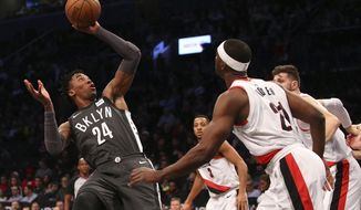 Brooklyn Nets forward Rondae Hollis-Jefferson (24) attempts an off balance shot against Portland Trail Blazers forward Noah Vonleh (21) during the first quarter of an NBA basketball game in New York, Friday, Nov. 24, 2017. (AP Photo/Rich Schultz)