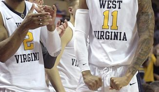 West Virginia guard Jevon Carter (2) and forward D'Angelo Hunter (11) celebrate on the bench after a basket by guard James Bolden during the second half of an NCAA college basketball game against Central Florida at the AdvoCare Invitational tournament Friday, Nov. 24, 2017, in Lake Buena Vista, Fla. (AP Photo/Phelan M. Ebenhack)