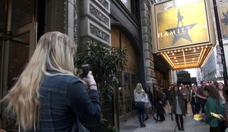"""In this photo taken Oct. 4, 2017, Alex Richards takes a photo of Meera Ganesh outside the CIBC Theatre after watching """"Hamilton: An American Musical"""" in Chicago. They were among the approximately 2,000 first year students at Northwestern University who got to see the show for free as part of the school's """"One Book One Northwestern"""" program. It's one of the ways colleges are using the hugely popular musical to teach students about history, art, critical thinking, performance, culture, and even politics. (AP Photo/Carrie Antlfinger)"""