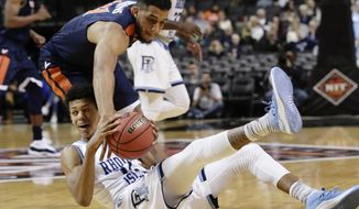 Virginia's Isaiah Wilkins (21) and Rhode Island's Jeff Dowtin (11) fight for control of the ball during the second half of an NCAA college basketball game in the championship round of the NIT Season Tip-Off tournament Friday, Nov. 24, 2017, in New York. (AP Photo/Frank Franklin II)