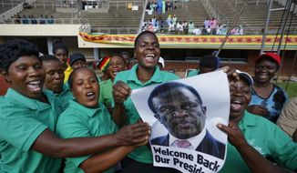 A band holds a picture of Mnangagwa and sings as they await his arrival at the presidential inauguration ceremony of Emmerson Mnangagwa in the capital Harare, Zimbabwe Friday, Nov. 24, 2017. Mnangagwa is being sworn in as Zimbabwe's president after Robert Mugabe resigned on Tuesday, ending his 37-year rule. (AP Photo/Ben Curtis)