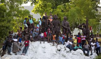 People sit on an independence heroes' monument after watching a ceremony marking the 214th anniversary of the battle that led to Haiti's independence from France, in Cap Haitien, Haiti, Saturday, Nov. 18, 2017. During the ceremony, the Haitian president officially reintroduced the army some 22 years after the national army was disbanded. (AP Photo/Dieu Nalio Chery)
