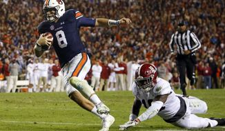 Auburn quarterback Jarrett Stidham (8) gets past Alabama linebacker Dylan Moses (18) to carry the ball in for a touchdown during the second half of the Iron Bowl NCAA college football game, Saturday, Nov. 25, 2017, in Auburn, Ala. (AP Photo/Butch Dill)