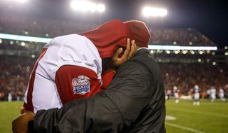 Alabama linebacker Shaun Dion Hamilton (20) hugs one of the team's coaches late in the second half of the Iron Bowl NCAA college football game against Auburn, Saturday, Nov. 25, 2017, in Auburn, Ala. Auburn won 26-14. (AP Photo/Butch Dill)