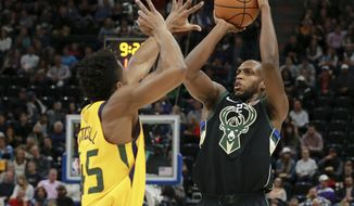 Milwaukee Bucks forward Khris Middleton (22) shoots past Utah Jazz guard Donovan Mitchell (45) during the first quarter of anNBA basketball game Saturday, Nov. 25, 2017, in Salt Lake City. (AP Photo/Chris Nicoll)