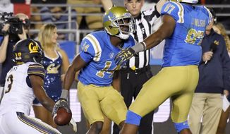 UCLA wide receiver Theo Howard, center, celebrates his touchdown with tight end Jordan Wilson, right, as California cornerback Elijah Hicks stands up during the first half of an NCAA college football game, Friday, Nov. 24, 2017, in Los Angeles. (AP Photo/Mark J. Terrill)