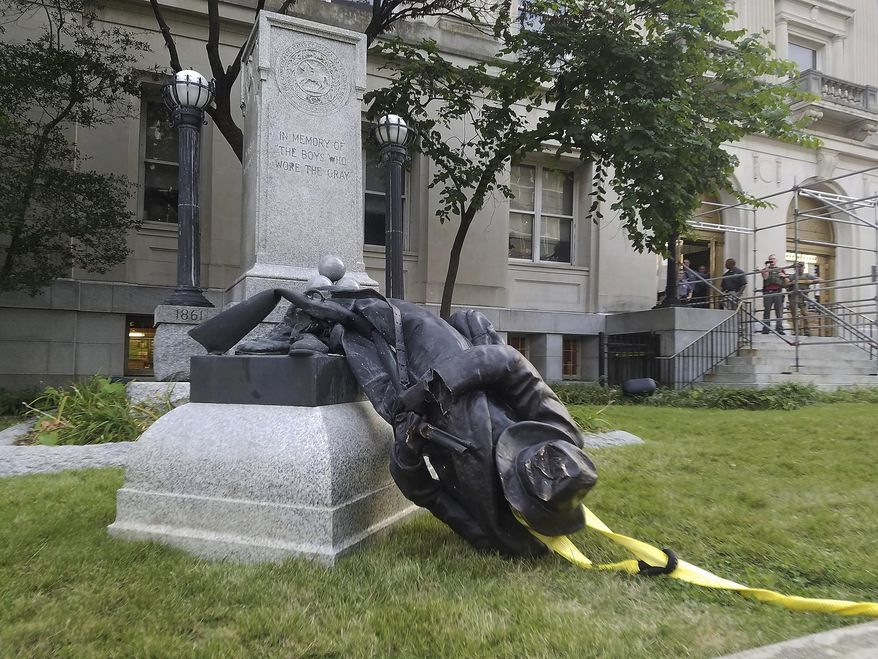 In this Aug. 14, 2017, file photo, a toppled Confederate statue lies on the ground in Durham, N.C. (Virginia Bridges/The Herald-Sun via AP, File)