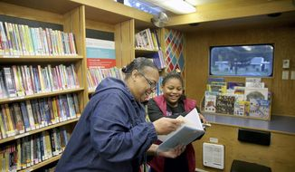 In this Thursday, Nov. 9, 2017. photo, Renee Thomas and her granddaughter Da-Mira, 9, look at library books from the bookmobile outside their new apartment in Bremerton, Wash. The pair were homeless and living in Renee's vehicle this summer. (Larry Steagall/Kitsap Sun via AP)