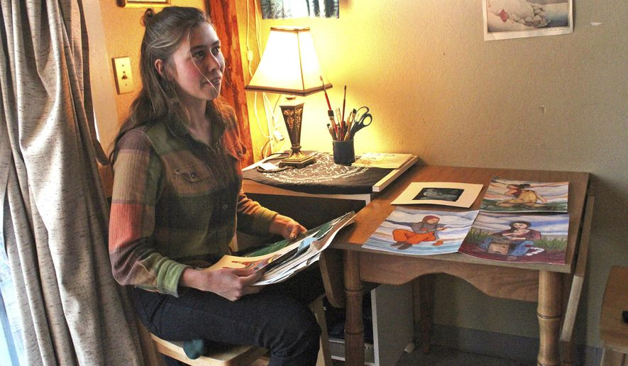 In this Nov. 10, 2017, photo, Oceana Wills, Oceana Wills, a local artist and commercial fisherman, goes through some of her paintings at the cabin where she's living in Kachemak City, Alaska. Wills has been drawing and creating art since she was young, but had her first official art show in Homer in 2016, followed by a few more. (Megan Pacer/Alaska Journal of Commerce via AP)