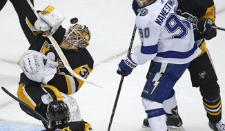 Pittsburgh Penguins' Tristan Jarry (35) blocks a shot in front of Tampa Bay Lightning's Vladislav Namestnikov (90) with Brian Dumoulin (8) defending during the first period of an NHL hockey game in Pittsburgh, Saturday, Nov. 25, 2017. (AP Photo/Gene J. Puskar)