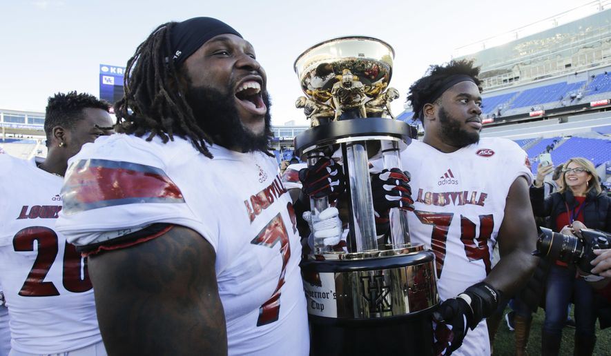 Louisville offensive lineman Lukayus McNeil, left, and offensive lineman Geron Christian carry the Governor's Cup trophy after Louisville defeated Kentucky 44-17 in an NCAA college football game, Saturday, Nov. 25, 2017, in Lexington, Ky. (AP Photo/David Stephenson) ** FILE **